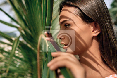 Fototapeta Young woman's face surrounded by tropical leaves. Woman face in profile with Natural nude make-up on a tropical leaf background. Natural cosmetic and wellness. Purity and skincare.