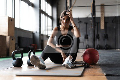 Fototapeta Young woman sitting on floor after her workout and looking down. Female athlete taking rest after fitness training