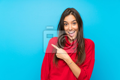 Fototapeta Young woman with red sweater over isolated blue background pointing finger to the side