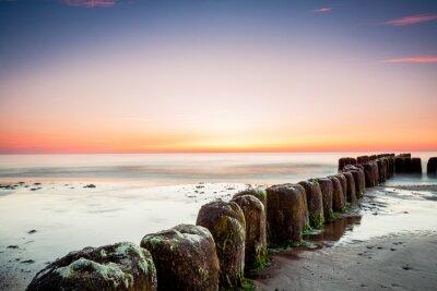Fototapeta Zachód słońca na morzu Bałtyckim, widok na stare pale falochronu.
