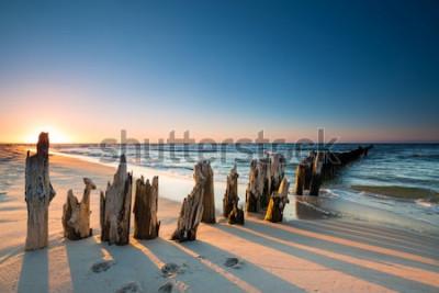 Fototapeta Zachód słońca na plaży nad Morzem Bałtyckim i stary drewniany falochron