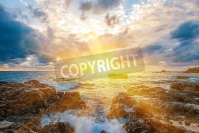 Fototapeta Zachód słońca na plaży z fal, morze, skały i dramatycznego nieba. Krajobraz ze słońcem w środku