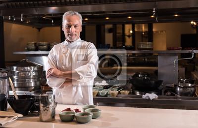 Fototapeta Zachwycony brodaty kucharz stojąc w kuchni restauracji