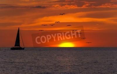 Fototapeta Żaglówka słońca fantazji z sulhouetted łodzi żaglowych na całej trasie aagainst jaskrawe kolorowe słońca z ptaków lecące w szyku przed pomarańczowym i żółtym kolorze wypełnione nieba.