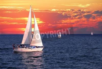 Fototapeta Żaglówka żeglowanie na spokojny wieczór z dramatycznego słońca
