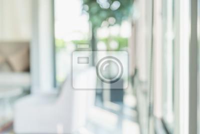 Fototapeta Zamazuje abstrakcjonistycznego tło kanapa w żywym pokoju przy dużym okno z bokeh światłem słonecznym.