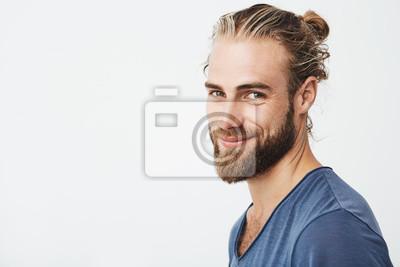 Fototapeta Zamknij się portret przystojny męski facet z brodą stwarzających w trzech kwartałach, patrząc w kamerę i szczęśliwie uśmiecha się. Koncepcja stylu życia.