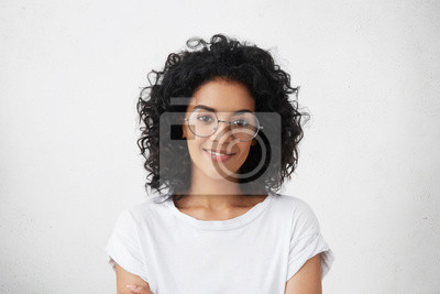 Fototapeta Zamknij studio strzał piękne kobiety młodych wyścigu mieszanych modelu z kręcone ciemne włosy spojrzenie na aparat fotograficzny z uroczy śliczny uśmiech podczas stwarzających przeciwko białego puste