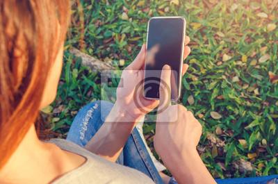 Fototapeta Zamyka w górę kobiety ręki używać mądrze telefon podczas gdy outdoors przy pogodnym wieczór