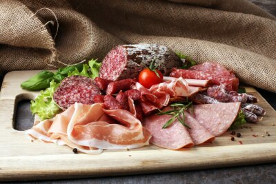 Zasobnik żywności z pysznym salami, kawałki szynki w plasterkach, kiełbasa, pomidory, sałatka i warzywa - taca mięsna z doborem