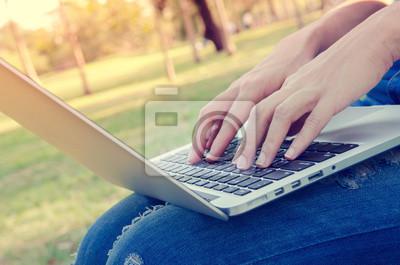 Fototapeta zbliżenie kobiety korzystają z komputera przenośnego odkryty o zachodzie słońca