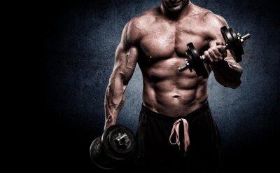 Fototapeta Zbliżenie młodych mięśni podnoszenia ciężarów mężczyzna na ciemnym backgrou
