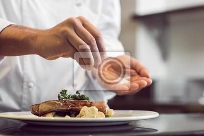Fototapeta Zbliżenie połowy sekcji kucharzem wprowadzenie soli