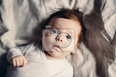 Fototapeta Zbliżenie portret ślicznego uroczego śmiesznego białej Kaukaskiej brunetki małego dziecka nowonarodzonego z błękitnymi szarymi oczami kłama na łóżku patrzeje w kamerze. Autentyczny styl życia szczery