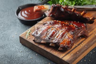 Fototapeta Zbliżenie żeberka wieprzowe z grilla z sosem BBQ i karmelizowane w miodzie. Smakowita przekąska piwo na drewnianej desce dla segregować na zmroku betonu tle