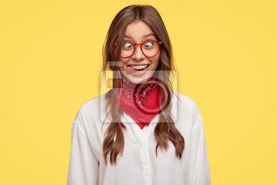 Fototapeta Zdjęcie szalonej dziewczyny robi śmieszną minę, krzyżuje oczy i wystaje z języka, bawi się głupcem, nie chce być odpowiedzialna, będąc w dobrym nastroju, modeluje wnętrze na żółtym tle studia.