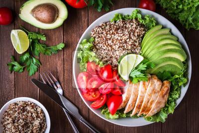 Fototapeta Zdrowa miska sałatka z quinoa, pomidorów, kurczaka, awokado, wapna i mieszanych zieleni (sałata, pietruszka) na drewnianym tle widok z góry. Żywność i zdrowie.