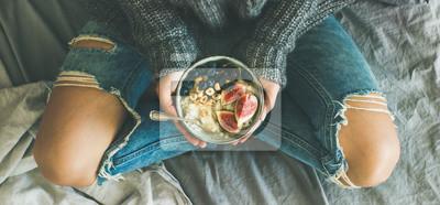 Fototapeta Zdrowe zimowe śniadanie w łóżku. Kobieta w sweter i dżinsy trzymając ryż owsianka kokosowe z fig, jagody, orzechy laskowe, widok z góry, szeroki skład. Czyste jedzenie, wegetariańska, koncepcja komfor
