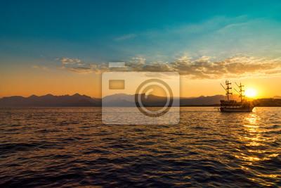 Żeglowanie statek na morzu przy zmierzch linią horyzontu.