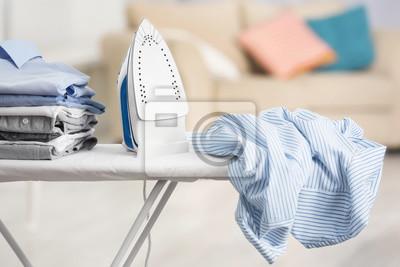 Fototapeta Żelazko elektryczne i stos ubrania na deskę do prasowania