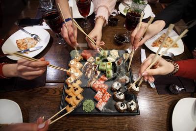 Fototapeta Zestaw rolek sushi na stole w restauracji. Partia przyjaciół je sushi rolki za pomocą bambusa.