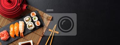 Fototapeta Zestaw sushi z wasabi, sos sojowy i czajniczek na czarnym tle kamienia
