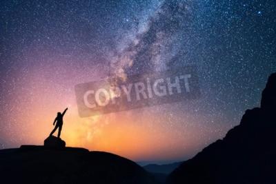 Fototapeta Złap gwiazdę. Osoba stoi obok Drogi Mlecznej wskazując na jasne gwiazdy.