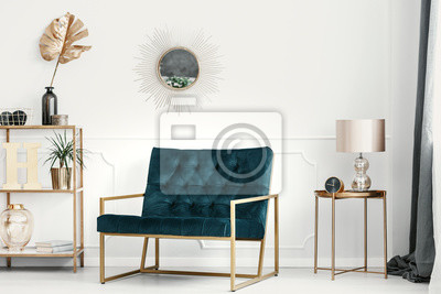 Fototapeta Złote ozdoby i meble w drogim wnętrzu salonu ze szmaragdową kanapą przy białej ścianie z listwą