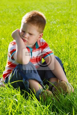 zły chłopak siedzi na trawie