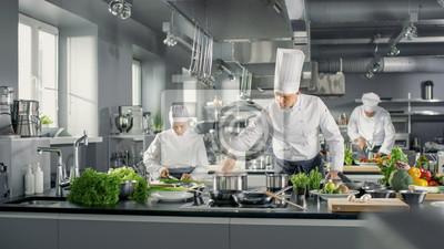 Fototapeta Znany szef kuchni działa w kuchni z dużą kuchnią z jego pomocą. Kuchnia jest pełna żywności, warzyw i gotowania dania.