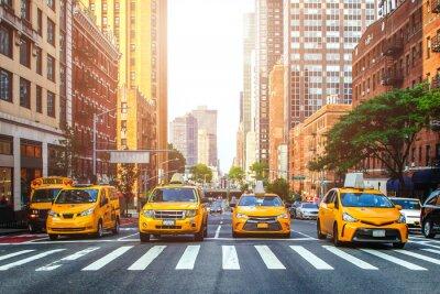 Fototapeta Żółte taksówki czeka zielone światło na rozdrożu ulic Miasto Nowy Jork podczas pogodnego lato dnia