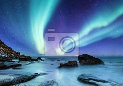 Fototapeta Zorza polarna na Lofotach w Norwegii. Nocne niebo z polarnymi światłami. Noc zimowy krajobraz z zorzą polarną i odbicie na powierzchni wody. Naturalne tło w Norwegii