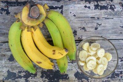 Naklejka A banch bananów i plasterki banana w filiżance szkła na drewnianym stole rocznika