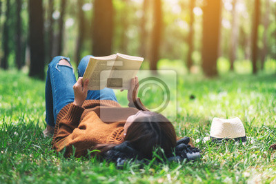Naklejka A beautiful Asian woman lying and reading a book in the park