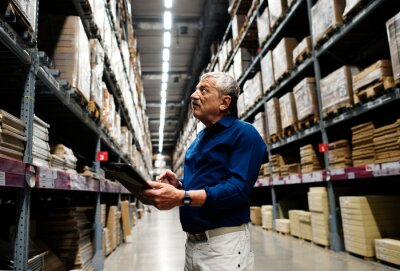 Naklejka A caucasian warehouse manager checking stock inventory
