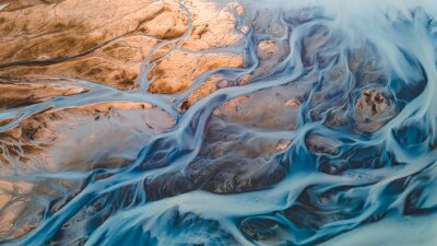 Naklejka A glacial rivers from above. Aerial photograph of the river streams from Icelandic glaciers. Beautiful art of the Mother nature created in Iceland. Wallpaper background high quality photo