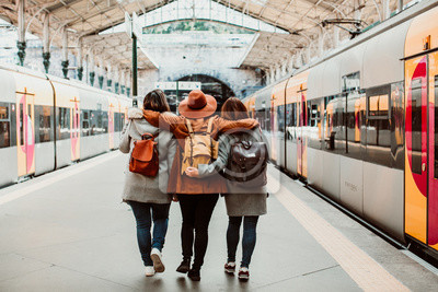 Naklejka .A group of young friends waiting relaxed and carefree at the station in Porto, Portugal before catching a train. Travel photography. Lifestyle.