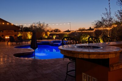 Naklejka A high definition view of a desert landscaped backyard in Mesa Arizona, with a pool spa, outdoor fireplace and Kitchen.