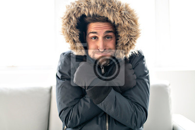 Naklejka A Man have cold on the sofa at home with winter coat