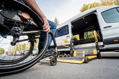 Naklejka A man in a wheelchair moves to the lift of a specialized vehicle