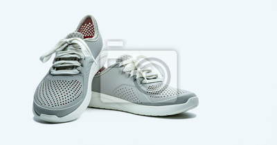 Naklejka A pair of grey shoes on white background. Comfortable shoes with pore. Breathable rubber shoes. Footwear.