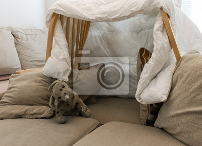 Naklejka A pillow fort made of blankets chairs with a stuffed animal in the living room.  Great for kids watching movies