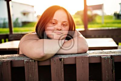 Naklejka A Portrait of trisomie 21 adult girl outside at sunset