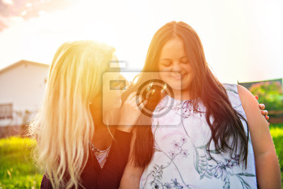 Naklejka A Portrait of trisomie 21 adult girl smilin outside at sunset with family friend