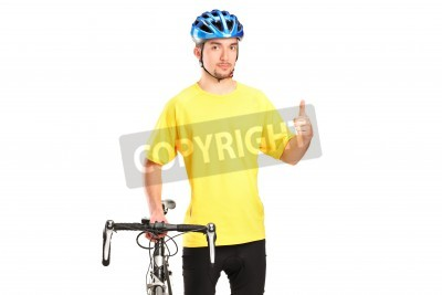 Naklejka A smiling bicyclist posing next to a bicycle and giving thumb up isolated on white background