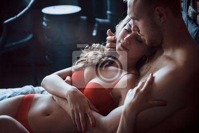 Naklejka A young couple are a boyfriend and a girlfriend who enjoys sleeping, lying in bed together in the daytime.