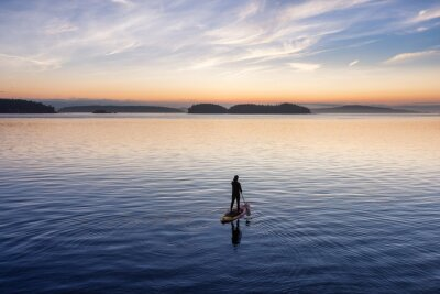 Naklejka Adventurous Caucasian Adult Woman on a Stand Up Paddle Board is paddling on the West Coast of Pacific Ocean. Sunny Sunrise Sky Art Render. Victoria, Vancouver Island, BC, Canada.