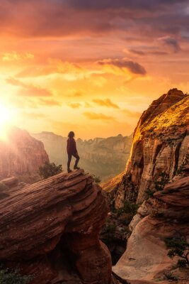 Naklejka Adventurous Woman at the edge of a cliff is looking at a beautiful landscape view in the Canyon. Sunset Sky Art Render. Taken in Zion National Park, Utah, United States.