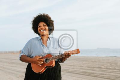 Naklejka African American musician playing ukulele at the beach