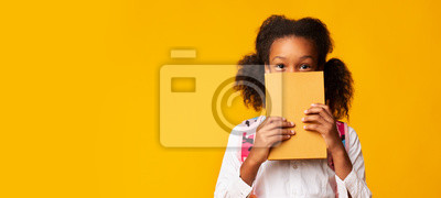 Naklejka African American Schoolgirl Covering Face With Book, Yellow Background